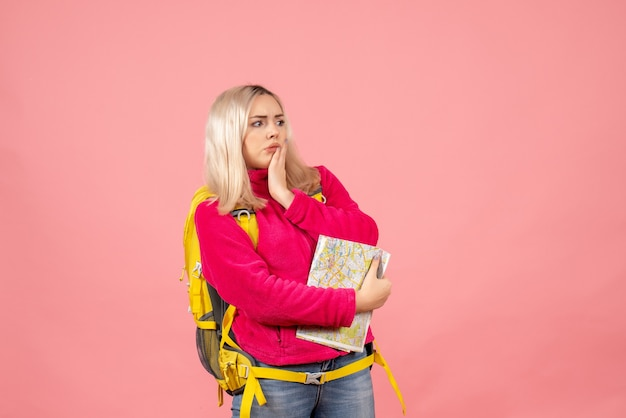 Mulher viajante com mochila amarela segurando o mapa