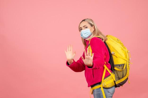 Mulher viajante com mochila amarela usando máscara e gesticulando na placa de pare