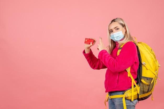 Mulher viajante com mochila amarela usando máscara segurando cartão fazendo arma de dedo