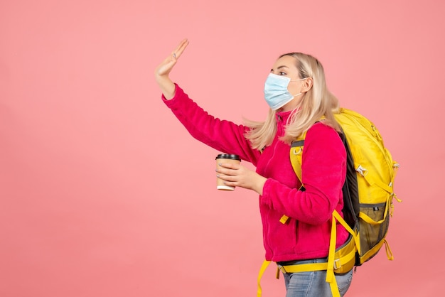 Mulher viajante com mochila amarela usando máscara segurando copo chamando alguém