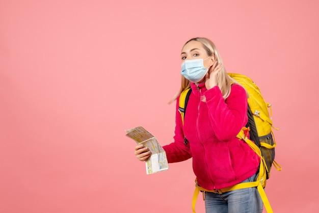 Mulher viajante com mochila amarela usando máscara segurando mapa e ouvindo algo