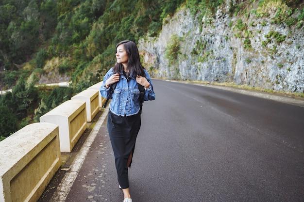 Mulher viajante com mochila, apreciando e caminhando na estrada nas montanhas