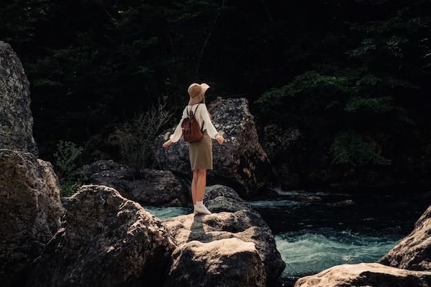 Mulher viajante com mochila e chapéu caminhando em incríveis montanhas e florestas perto de um rio com águas azuis profundas