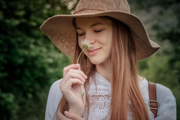 Mulher viajante com mochila e chapéu caminhando em um lindo campo de camomilas incrível
