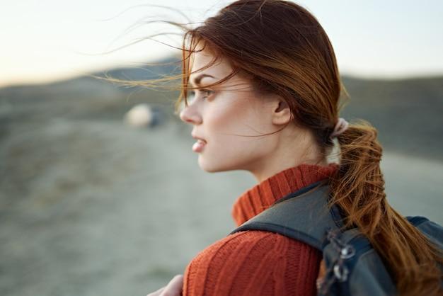 Mulher viajante com mochila nas costas nas montanhas ao ar livre olhando para o lado