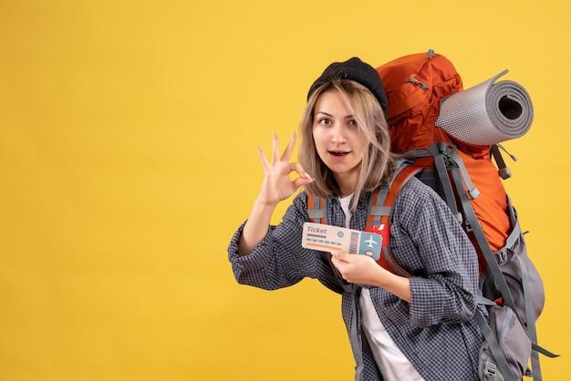 Mulher viajante com mochila segurando bilhete fazendo sinal de ok