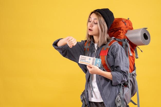Mulher viajante com mochila segurando bilhete verificando o tempo