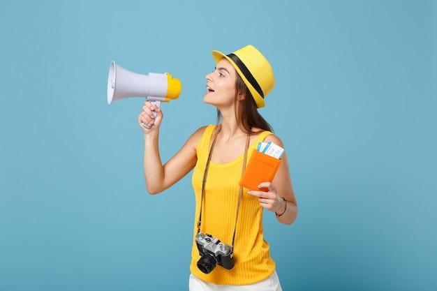Mulher viajante com roupas casuais amarelas e chapéu segurando a câmera do megafone de bilhetes azul