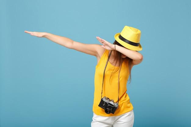 Mulher viajante com roupas casuais de verão amarelo e chapéu com câmera fotográfica azul