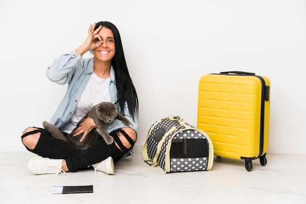 Mulher viajante com seu gato isolado no branco animado, mantendo o gesto ok no olho.