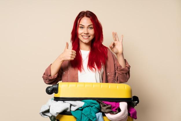 Mulher viajante com uma mala cheia de roupas isoladas na parede bege mostrando sinal ok e polegar para cima gesto