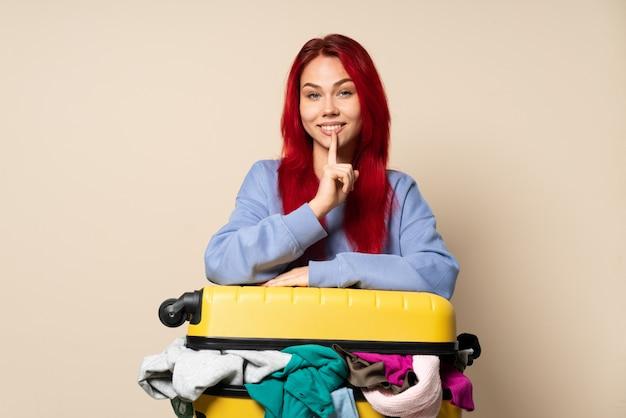 Mulher viajante com uma mala cheia de roupas isoladas na parede bege, mostrando um sinal de gesto de silêncio colocando o dedo na boca