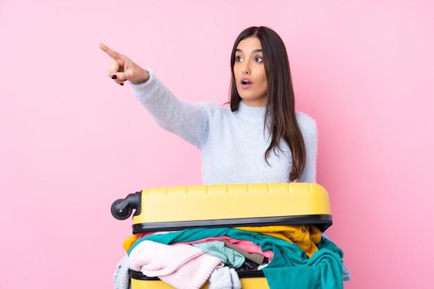 Mulher viajante com uma mala cheia de roupas isolado parede rosa apontando para fora
