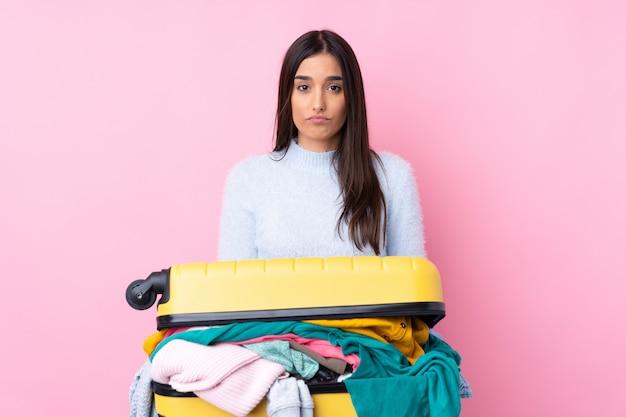Mulher viajante com uma mala cheia de roupas isolado parede rosa triste