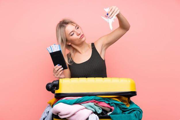 Mulher viajante com uma mala cheia de roupas isolado parede rosa