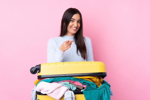 Mulher viajante com uma mala cheia de roupas sobre parede rosa isolada aponta o dedo para você