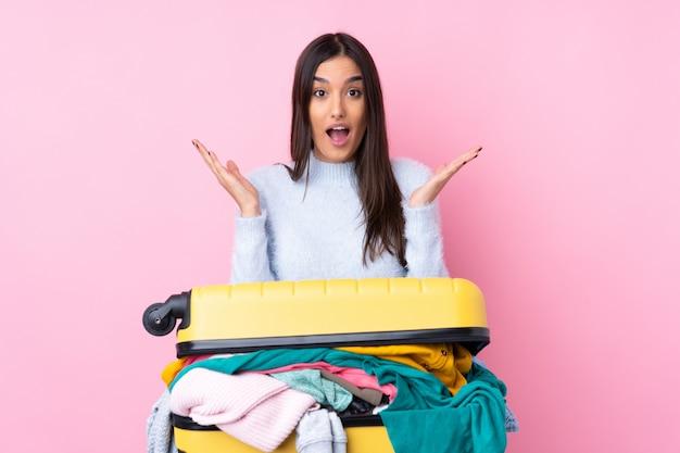 Mulher viajante com uma mala cheia de roupas sobre parede rosa isolada com expressão facial de surpresa