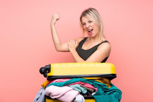 Mulher viajante com uma mala cheia de roupas sobre parede rosa isolada, fazendo um gesto forte