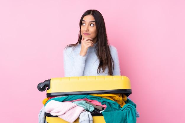 Mulher viajante com uma mala cheia de roupas sobre parede rosa isolada, pensando uma idéia