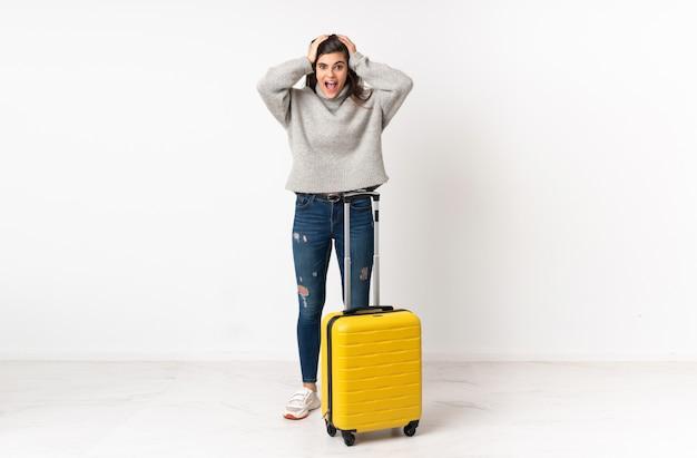 Mulher viajante com uma mala na parede branca com expressão facial de surpresa