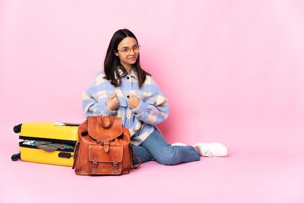 Mulher viajante com uma mala sentada no chão apontando para si mesma