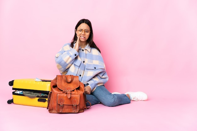 Mulher viajante com uma mala sentada no chão com dor de dente