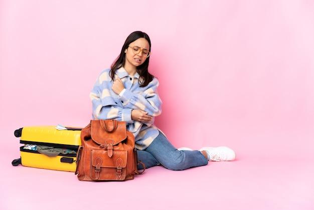 Mulher viajante com uma mala sentada no chão e com dor no cotovelo