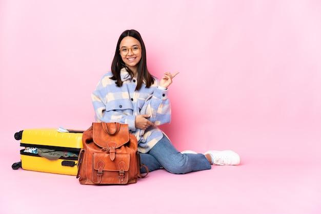 Mulher viajante com uma mala sentada no chão feliz e apontando para cima