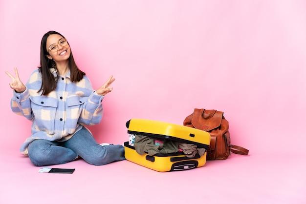 Mulher viajante com uma mala sentada no chão, mostrando o sinal da vitória com as duas mãos
