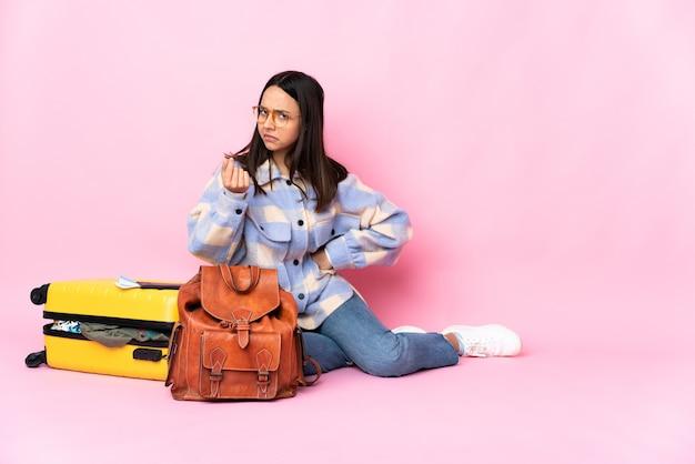 Mulher viajante com uma mala sentada no chão