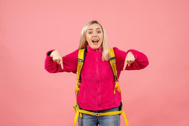 Mulher viajante com vista frontal com mochila amarela apontando com os dedos para baixo