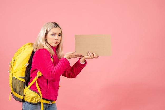 Mulher viajante com vista frontal com mochila amarela segurando um papelão