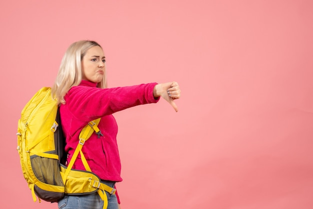 Mulher viajante com vista frontal com mochila apontando para baixo