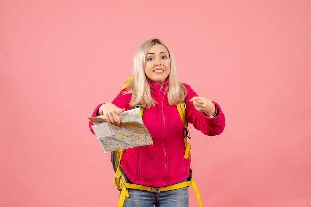 Mulher viajante com vista frontal em roupas casuais usando mochila segurando mapa apontando