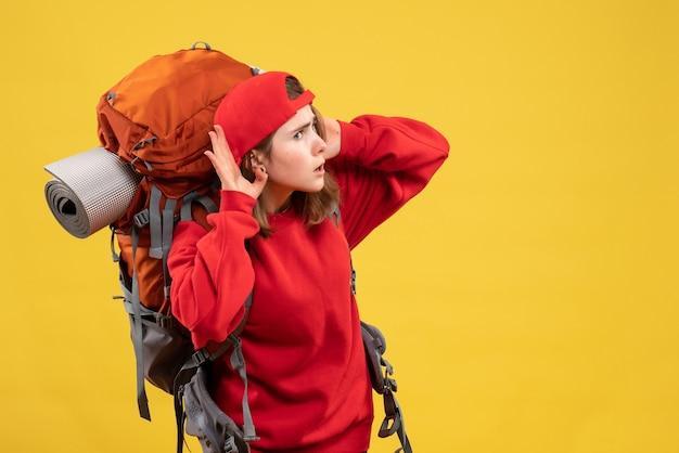 Mulher viajante curiosa com mochila ouvindo alguma coisa de frente