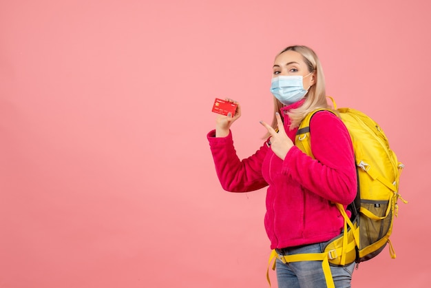 Mulher viajante de vista frontal com máscara segurando cartão fazendo sinal de vitória