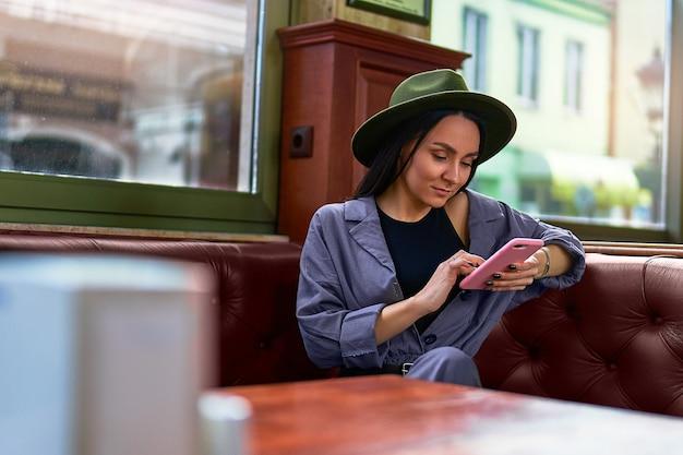 Mulher viajante elegante elegante fofo atraente hipster com chapéu de feltro e telefone