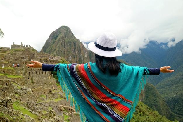 Mulher viajante em poncho abrindo os braços para a antiga cidadela inca de machu picchu