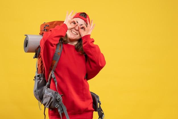 Mulher viajante feliz com a mochila na frente colocando a placa de ok na frente dos olhos