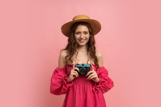 Mulher viajante feliz com chapéu de palha e vestido rosa segurando uma câmera retro rosa