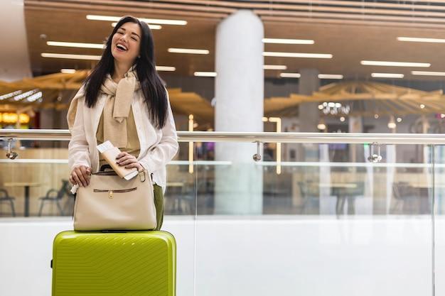 Mulher viajante feliz com documentos e passagem aguardando partida no terminal do aeroporto internacional