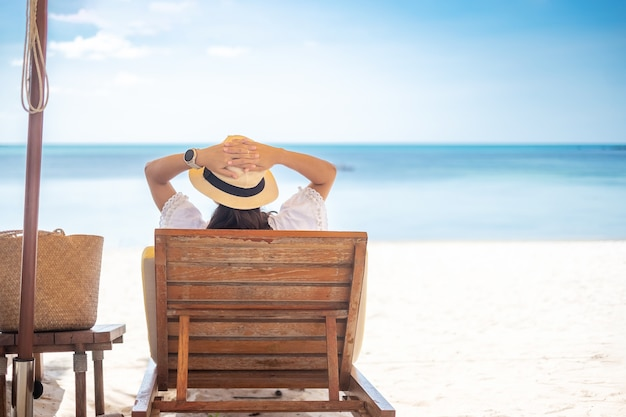 Mulher viajante feliz com vestido e chapéu branco aprecia a bela vista do mar