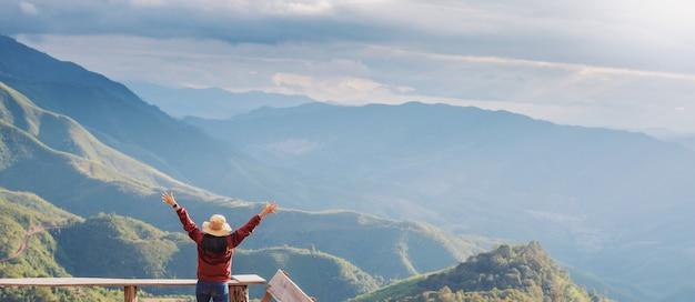 Mulher viajante feliz em pé e levantar as mãos para mostrar sucesso no topo da montanha