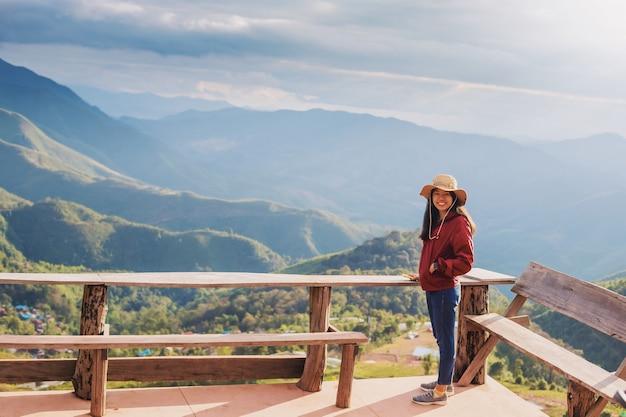 Mulher viajante feliz no topo da montanha