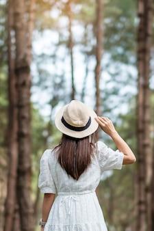 Mulher viajante feliz vista traseira em pé e olhando para um fundo de floresta de pinheiros turva
