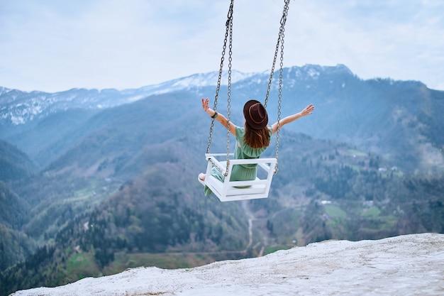 Mulher viajante livre com braços abertos desfrutando de balançar em um balanço celestial e vista para a montanha. momento calmo e tranquilo do conceito de desejo por viagens quando a pessoa sente felicidade e liberdade