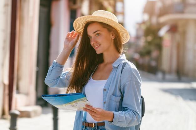 Mulher viajante no chapéu, procurando a direção certa no mapa de viagem enquanto viaja pela europa. estilo de vida de férias e viagens