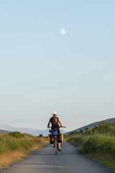 Mulher viajante pedalando em uma estrada rural com a lua ao fundo