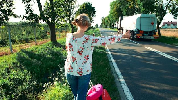 Mulher viajante pedindo carona em uma estrada ensolarada e caminhando. mulher jovem mochileiro feliz procurando uma carona para iniciar uma viagem em uma estrada rural iluminada pelo sol.