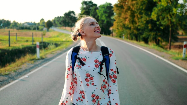Mulher viajante pegando sua mochila mulher mochileira levanta sua bolsa da estrada pela manhã c ...